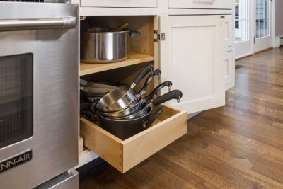 Single roll-out tray in a base cabinet, storing pots and saucepans. Shown in CliqStudios Dayton White.